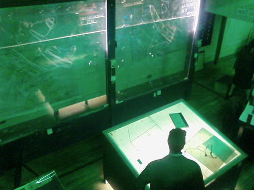 IMAGE: Looking down into a control room within the bunker, lit with green lights.