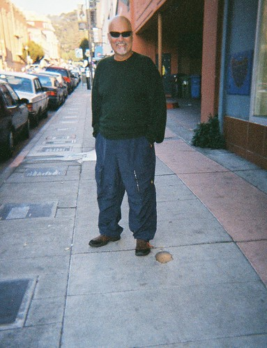 Alfred Arteaga stands next to his poetry plaque in Berkeley