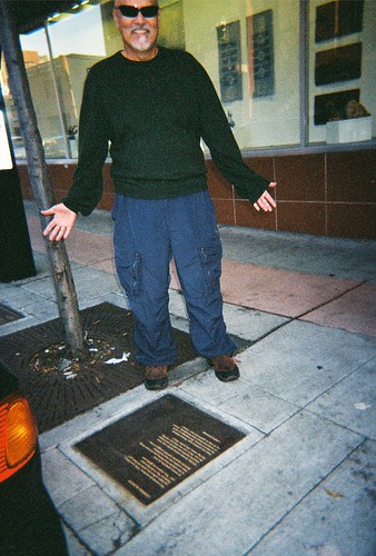 Alfred Arteaga next to his poetry plaque, Berkeley