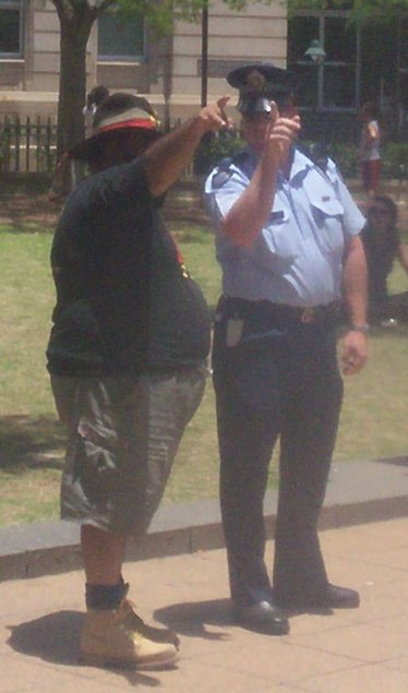 Sam Watson, rally organiser, discusses details with a police senior-sergeant 2 - Justice for Mulrunji Rally at Queens Park and March through Brisbane City, Australia, November 18 2006