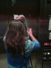 Mary removes a sign in the elevator