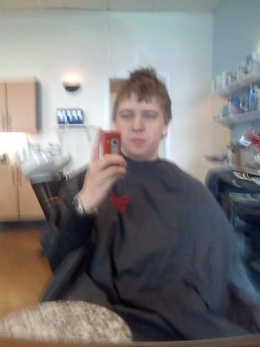 David i frisörstolen före ingreppet med en mobiltelefon i handen