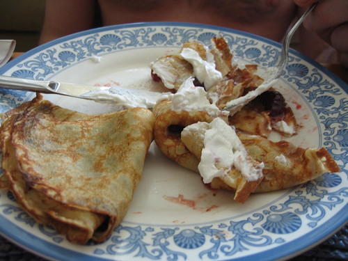 Devouring of crepes with a dollop of whipped topping