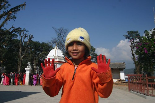 Girl with red hands after playing with the colours used at the temple ceremonies