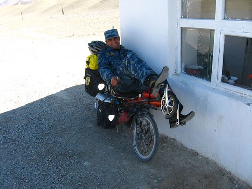 A checkpoint guard tries out the recumbent - near Murghab, Tajikistan / 軍人がリカンベントに乗る(タジキスタン、ムルガブ町)
