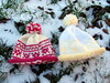 Two Fair Isle baby hats on a snowy day
