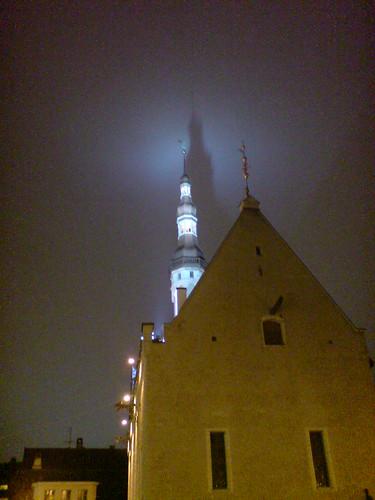 Los focos del viejo ayuntamiento de Tallinn lanzan su sombra contra las nubes