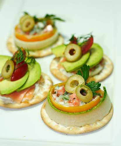Front: Carrot and cucumber dressed with yogurt and mayoinaise with green olives on table water crackers