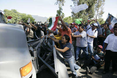 Un camión que transportaba a elementos de la PFP avanza sobre las barricadas que miembros y seguidores de la APPO colocaron para impedir su entrada