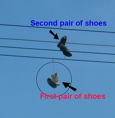2 pairs of shoes hanging on a line..