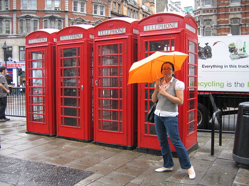 Singin' in the rain by London's trademark phone booths!