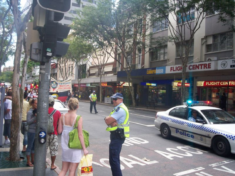 Policeman explains the hold up to a shopper as the march approaches the corner of Adelaide and Edward Sts - Justice for Mulrunji Rally at Queens Park and March through Brisbane City, Australia, November 18 2006