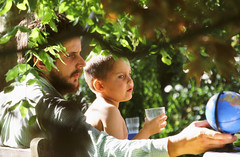 Sebastian looks at a globe with his son under an apple tree in Nigel and Honor's garden