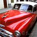 A red classic car sits in Havana