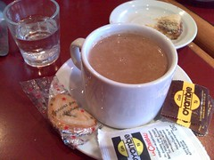 Hot chocolate with bags of sugar and sweetener