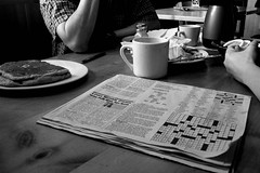 Photo from weekly breakfast at Seward Cafe, with food, elbows, and a newspaper on the table