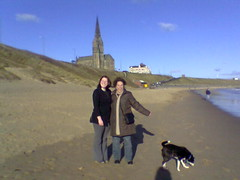 Elly, Molly and Tara on the beach, with cliffs and church in the background