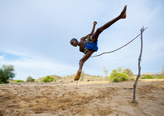 Mukubal Kid Doing High Jumping, Virie Area, Angola photo by Eric Lafforgue