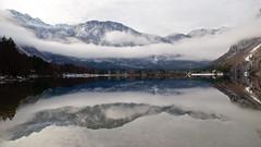 Lake under mountains and clouds photo by Karmen Smolnikar