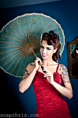 Pretty Tattooed Redhead Pinup model wearing a red swimsuit and a parasol photo by tibchris