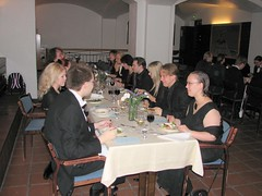 People sitting at a long table, enjoying the food