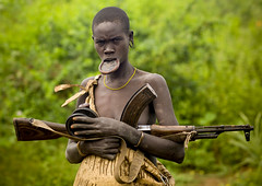 Mursi woman and Kalashnikov Ethiopia photo by Eric Lafforgue