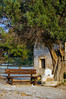 Empty wooden bench near ancient Greek chapel