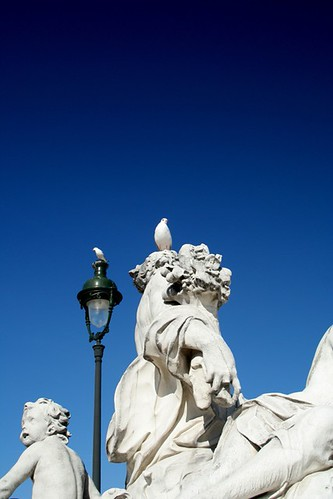 two birds on one statue and one lampost