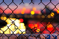 Pink Sunrise Mass Pike Bokeh in Allston, through Chain Link Hole facing Boston photo by Greg DuBois Photography