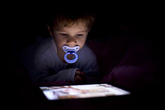 Portrait of a small boy looking a tablet in the dark photo by Nasos Zovoilis