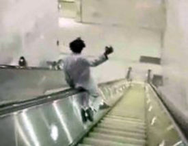 Man sliding down escalator