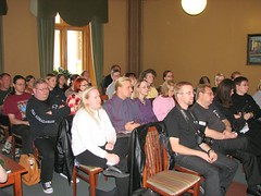 People sitting in the audience, listening to a presentation