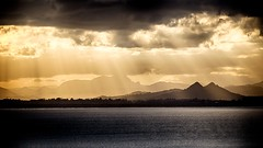 Sunbeams over volcanic mountains photo by rikpiks