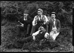 Four well-dressed men holding beer bottles photo by Powerhouse Museum Collection