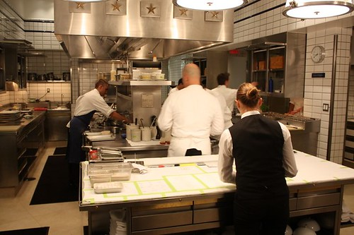 The main kitchen from the front, with the head chef in all white in the foreground