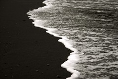 white surf, black sand photo by van Ort