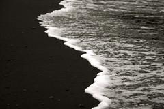 white surf, black sand photo by van Ort