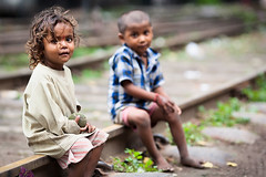 Girl and boy sit on railway tracks and Delhi, India photo by damonlynch