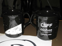 The front and back views of the LSFF mug: moon surface, and LSFF & ConFuse logos