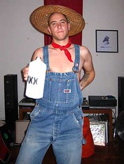 Jacob with straw hat, bandanna, dungarees and bottle of moonshine