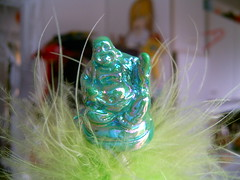 shiny green plastic buddha on a spring