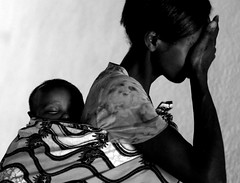 A weeping mother with baby on her back in Rwanda photo by Samer M