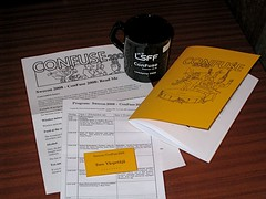 Convention booklet, program leaflet, badge, readme flyer and the con mug laid out in a folded stack on a table