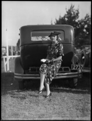 Woman sitting on bumper bar of a car at Warwick Farm racecourse photo by Powerhouse Museum Collection