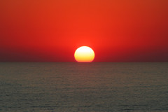 The setting sun dips into the Mediterranean sea photo by Jay Tilston