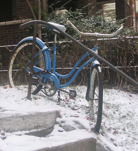 Bike chained to fence in snow