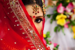 Bride covering eyes with veil photo by insane_capture