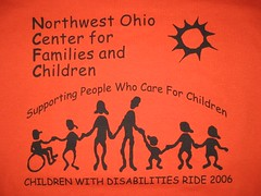 row of cartoon silhouette people holding hands, one in wheelchair, six standing. some seen to be children, some adults