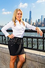 Low Angle View of an Attractive Blond Woman in White Blouse and Black Skirt, Standing and Relaxing with one hand on Hip, Jersey City, New Jersey photo by George Oze