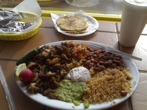 Clockwise from bottom: Carnitas Plate, extra tortillas, a pupusa, and orchata